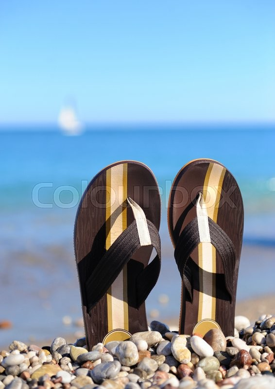 Stock image of 'Beach flip flops on tropical sand'