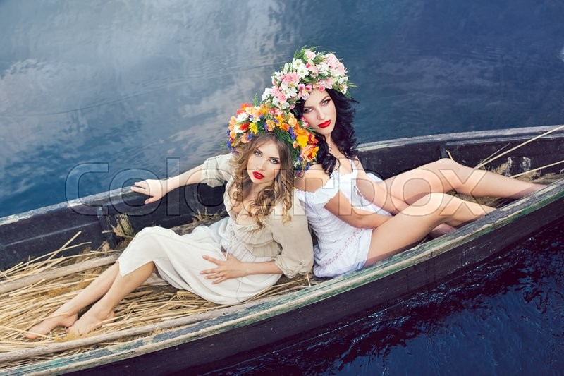 Stock image of 'Two young women on boat at sunset. The girls has a colorfull make-up and flower wreath on they head, relaxing and sailing on the river. Beautiful sexy slim body and cute face. Fashion art photography. Concept of female beauty, rest on the nature, and water travel'