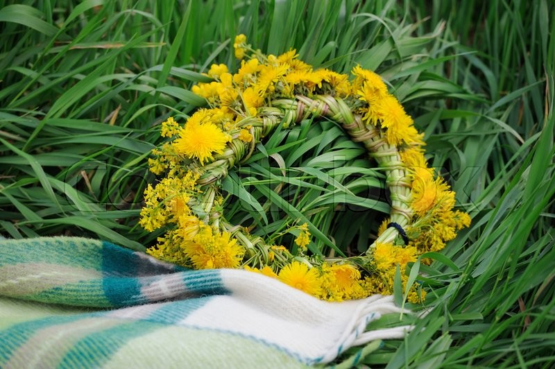 Stock image of 'Flower wreath with yellow blooming flowers in grass'