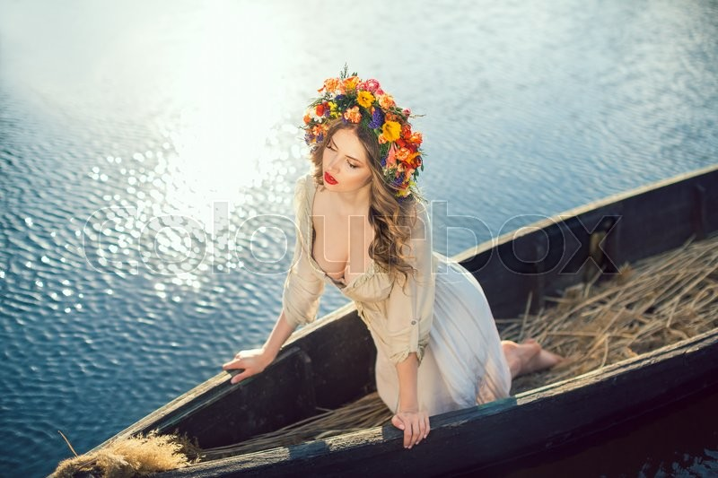 Stock image of 'Young gorgeous woman on boat at sunset. The girl has colorfull make-up a flower wreath on her head, relaxing and sailing on river. Beautiful body and face. Fashion art photography. Concept of female beauty, rest in the nature, and water travel'