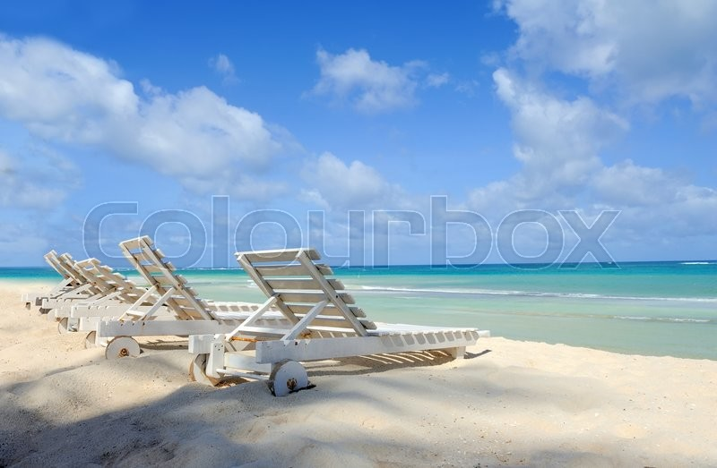Stock image of 'Tropical beach with a sun-lounger facing the blue sea'