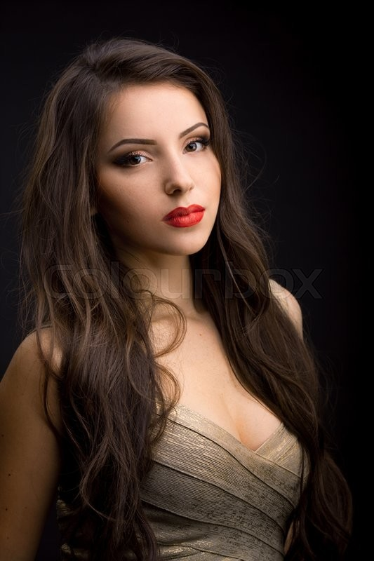 Stock image of 'Serious brunette woman in evening dress with beautiful make-up posing on black background. Looking at camera'