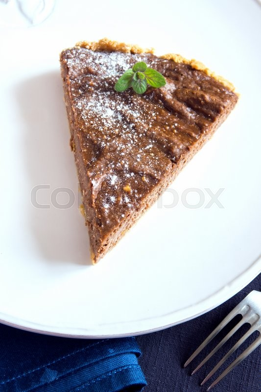 Stock image of 'Homemade chocolate pie (cheesecake) with mint on white plate close up'