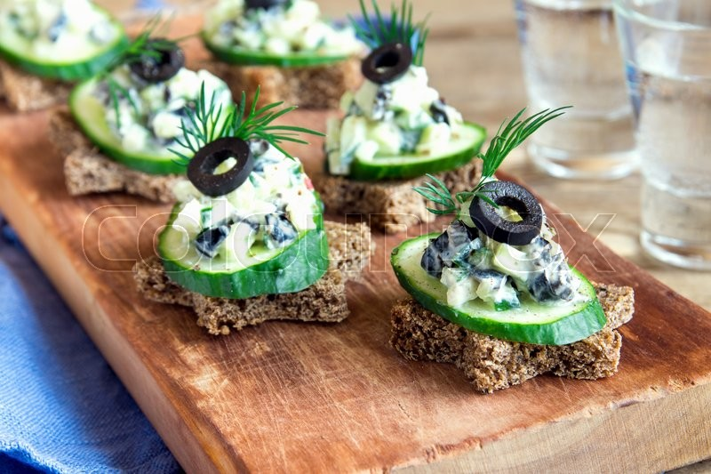 Stock image of 'Mini sandwiches (snacks) with cucumber, olives and fish salad over rustic wooden background'