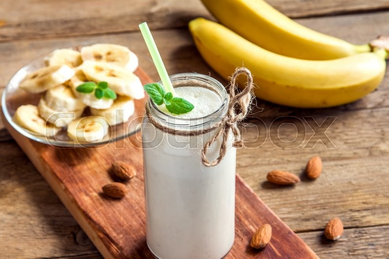 Stock image of 'Banana smoothie with mint and almond over rustic wooden background'