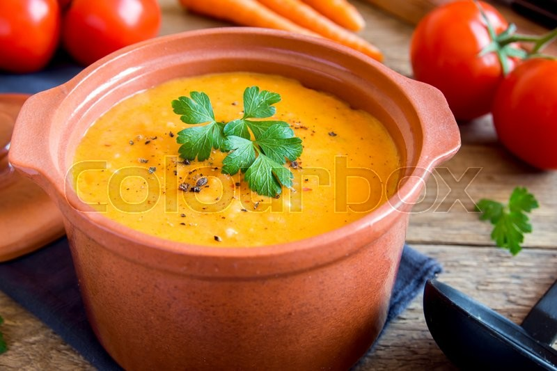 Stock image of 'Vegetable tomato and carrot soup in ceramic pot and ingredients over rustic wooden background '