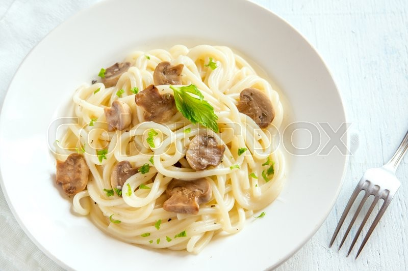 Stock image of 'Spaghetti pasta with grilled mushrooms and greens on white plate'