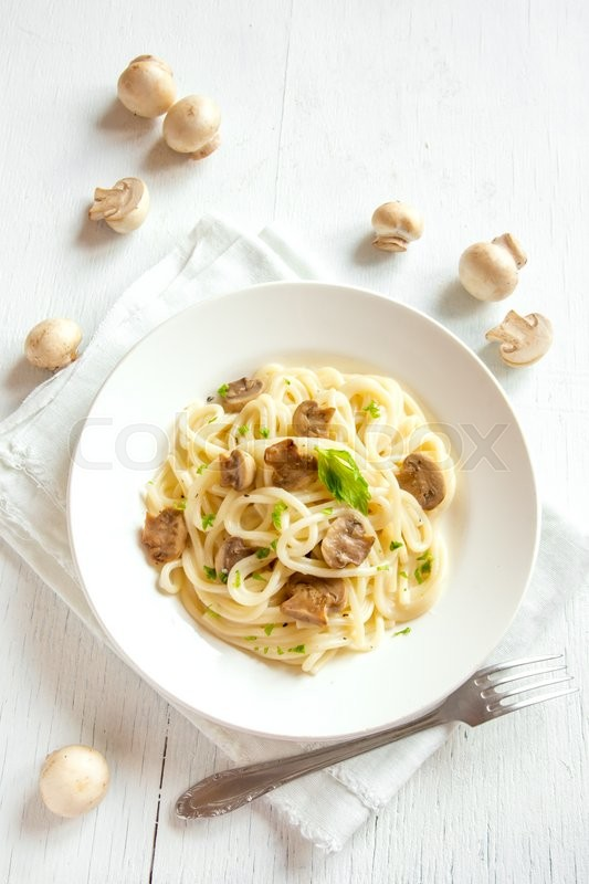 Stock image of 'Spaghetti pasta with grilled mushrooms and greens on white wooden background'