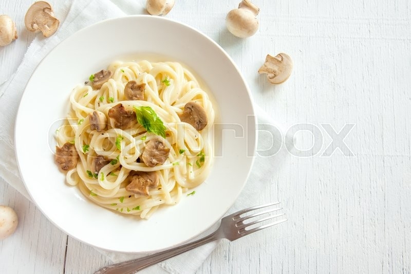 Stock image of 'Spaghetti pasta with grilled mushrooms and greens on white wooden background with copy space'