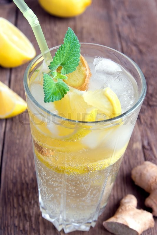 Stock image of 'Ginger ale soda with lemon, mint, ginger and ice over rustic wooden background'