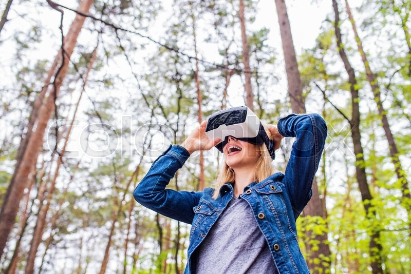 Stock image of 'Blond woman wearing virtual reality goggles outside in green forest, spring nature'