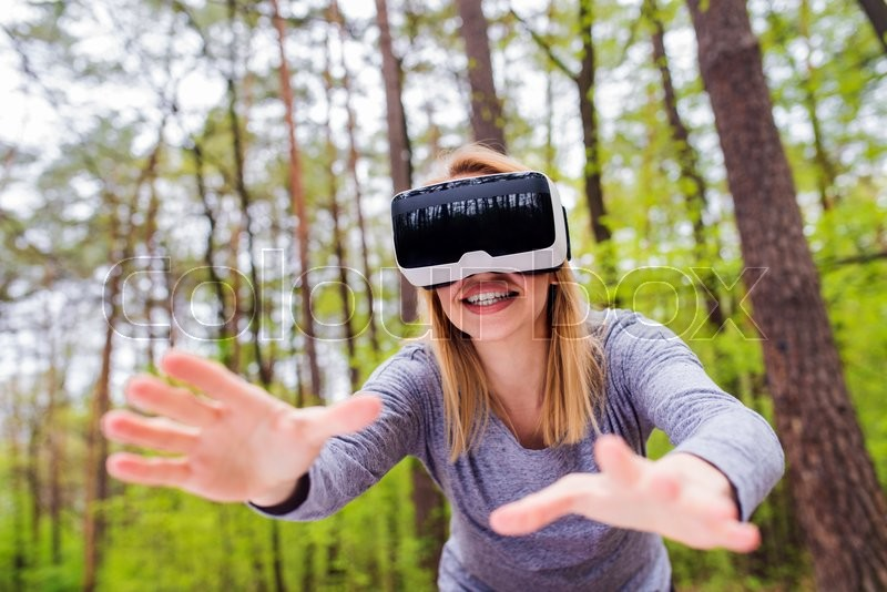 Stock image of 'Blond woman wearing virtual reality goggles outside in spring nature'