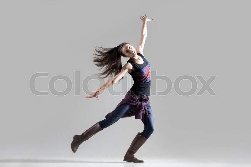 Stock image of 'Stylish dancing young woman portrait. Fit girl wearing English flag tank top warming up, working out. Happy dancer spinning on one leg with her ponytail flying. Studio image. Grey background'