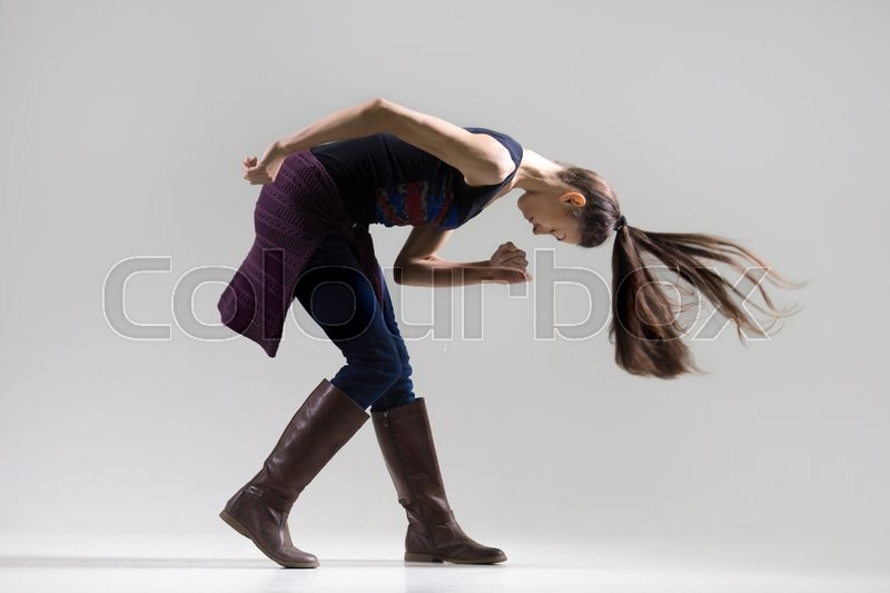 Stock image of 'Profile portrait of stylish young woman dancing with closed eyes. Fit girl wearing casual clothing working out. Studio image. Grey background. Full length'