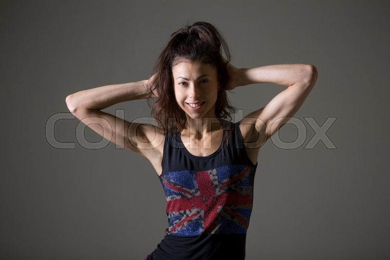 Stock image of 'Stylish sporty young woman lifestyle portrait. Fit girl wearing English flag tank top looking at camera. Happy caucasian female athlete posing. Studio image. Dark background'