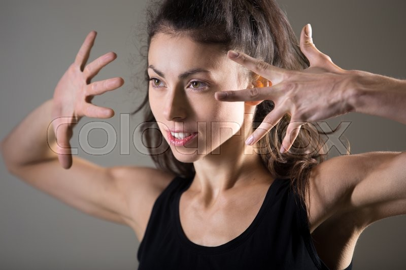 Stock image of 'Stylish sporty young woman lifestyle portrait. Fit girl dancing. Happy caucasian female athlete posing. Studio image. Dark background'