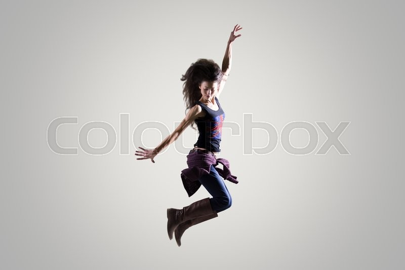 Stock image of 'Dancing young woman portrait. Fit sporty girl wearing English flag tank top warming up, working out and jumping in the air with her long hair flying. Studio image. Grey background'