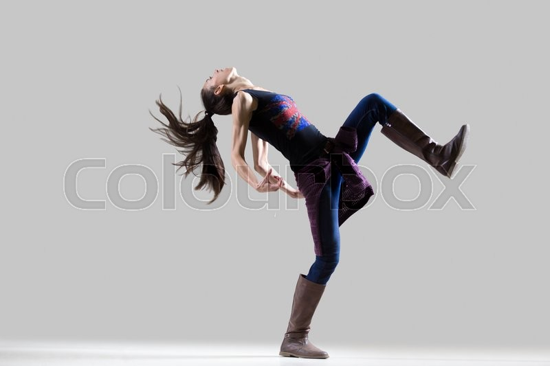 Stock image of 'Stylish dancing young woman portrait. Fit sporty girl wearing English flag tank top warming up, working out with her long ponytail flying. Studio image. Grey background. Full length'