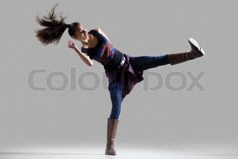 Stock image of 'Stylish dancing young woman portrait. Fit athletic girl wearing British flag tank top warming up, working out with her long ponytail flying. Studio image. Grey background'