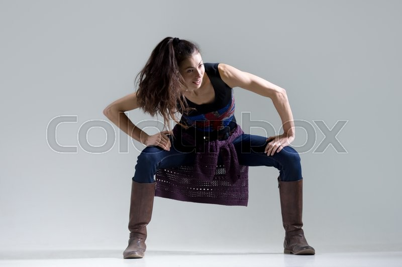 Stock image of 'Stylish happy dancing young woman portrait. Fit smiling girl wearing English flag tank top warming up, working out. Studio image. Grey background. Full length'