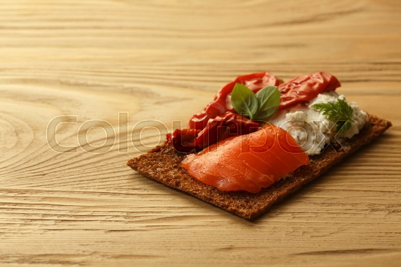 Stock image of 'Bread crisp (crispbread open-faced sandwich) with salmon, soft cream cheese, sun dried tomatoes and fresh chervil. Selective focus'