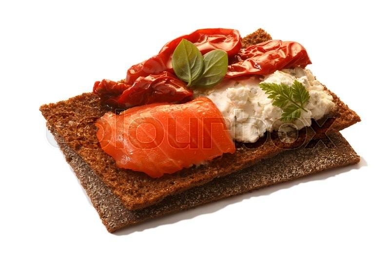 Stock image of 'Bread crisp (crispbread open-faced sandwich) with salmon, soft cream cheese, sun dried tomatoes and fresh chervil. Clipping paths for both crisp and shadow, infinite depth of field'