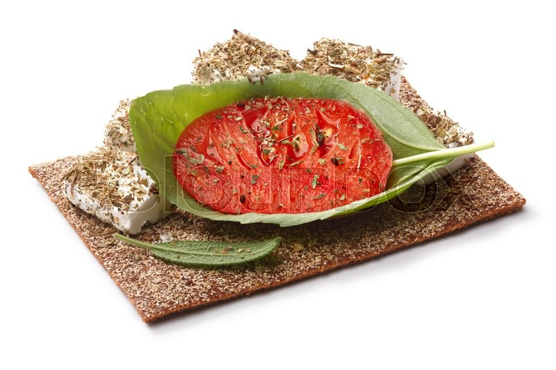 Stock image of 'Bread crisp (crispbread open-faced sandwich) with heirloom tomato, soft cream cheese and fresh basil leaves. Clipping paths for both crisp and shadow, infinite depth of field'