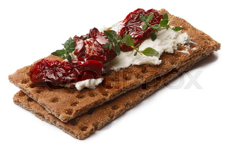 Stock image of 'Bread crisp (crispbread open-faced sandwich) with sun-dried tomatoes, cream cheese and fresh thyme. Clipping paths for both crisp and shadow, infinite depth of field'