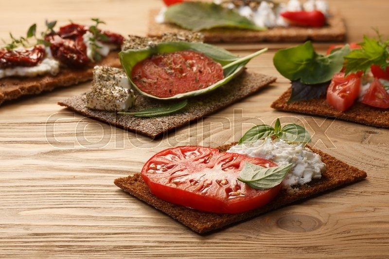 Stock image of 'Bread crisp (crispbread open-faced sandwich) with heirloom tomato, cream cheese and fresh basil leaves on wooden table. Selective focus on foreground sandwich'