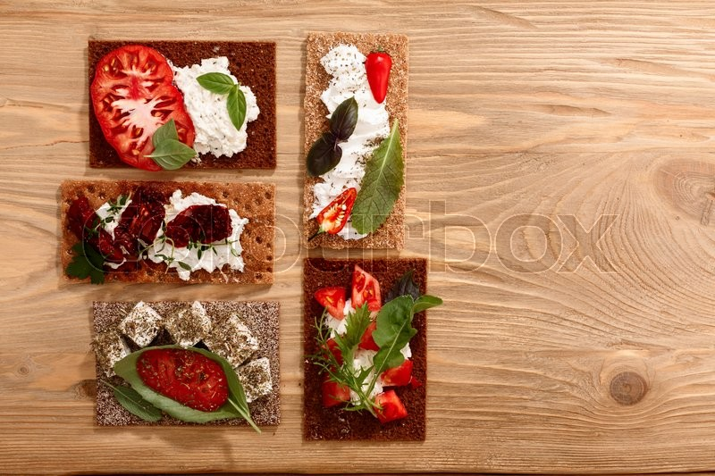 Stock image of 'Different bread crisps (crispbread open-faced sandwiches) with both fresh and dried heirloom tomatoes, cream cheese and fresh greens. Above view, flat lay'