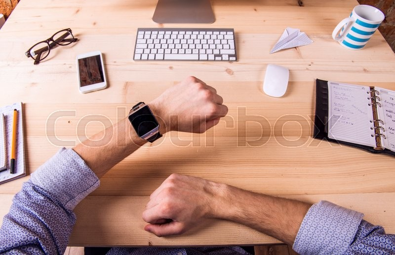 Stock image of 'Businessman at the desk, wearing smart watch, working.  Computer, smart phone and various office supplies around the workplace.'
