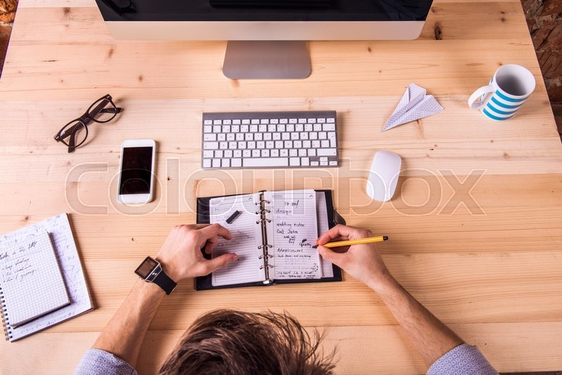 Stock image of 'Businessman at the desk, wearing smart watch, writing into personal organizer.  Computer, smart phone and various office supplies around the workplace.'