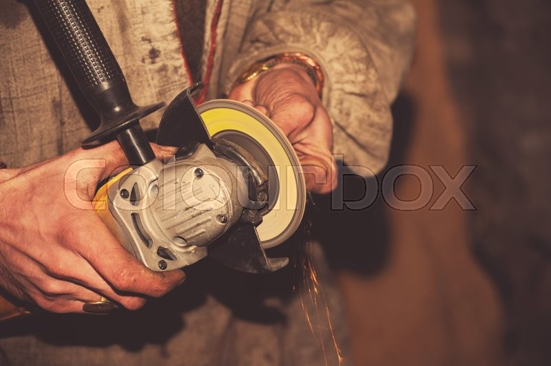 Stock image of 'angle grinder in hand working '
