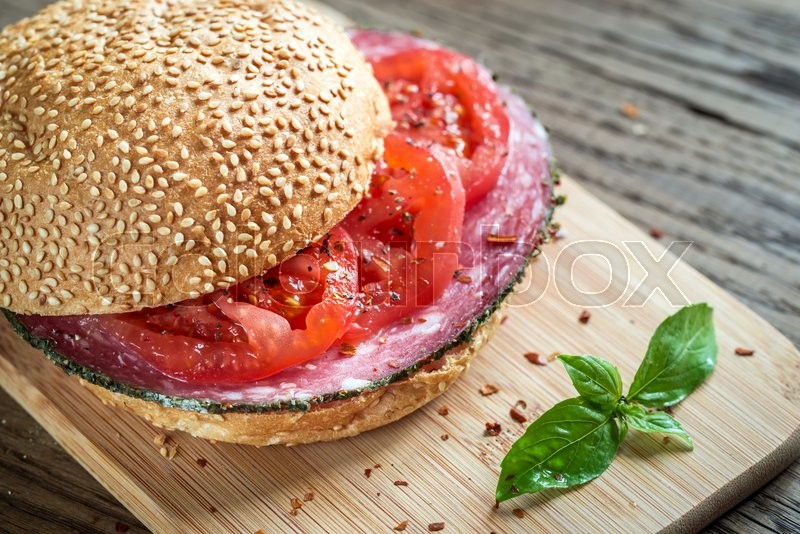 Stock image of 'Sandwich with salami and tomatoes'