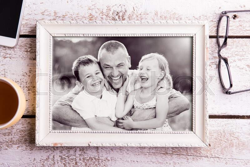 Stock image of 'Fathers day composition. Black and white picture of father holding his children in picture frame. Studio shot on white wooden background.'