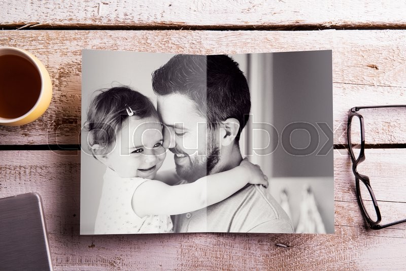 Stock image of 'Fathers day composition. Black and white picture of father holding his little daughter. Studio shot on white wooden background.'