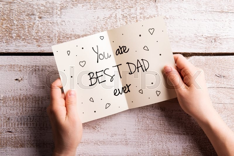 Stock image of 'Hands of unrecognizable man holding Fathers Day greeting card. Studio shot on white wooden background.'