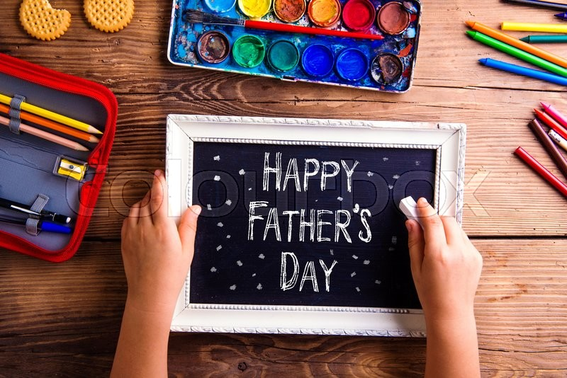 Stock image of 'Fathers day composition. Hands of unrecognizable child writing with chalk on black board in white picture frame. Studio shot on wooden background.'
