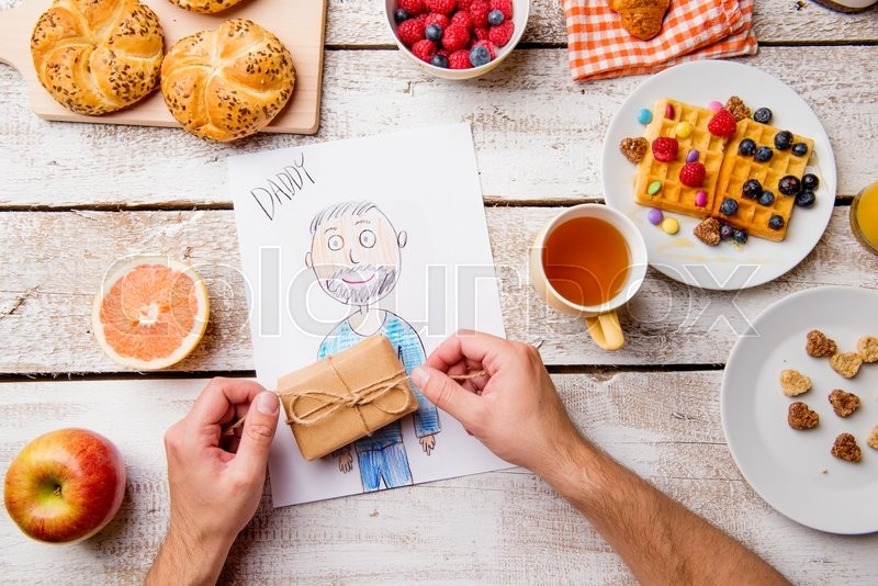 Stock image of 'Fathers day composition. Hands of unrecognizable man with his childs drawing of him, unpacking little present. Breakfast waffles with fruit. Studio shot on wooden background.'