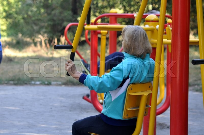 Stock image of 'An old woman making sport outdoors'