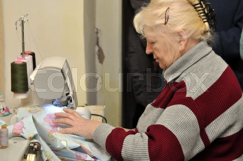 Stock image of 'An old woman working on overlock'