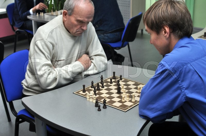 Stock image of 'An old man and aboy playing chess'