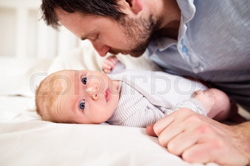 Stock image of 'Cute newborn baby boy lying on a bed, held by his father'