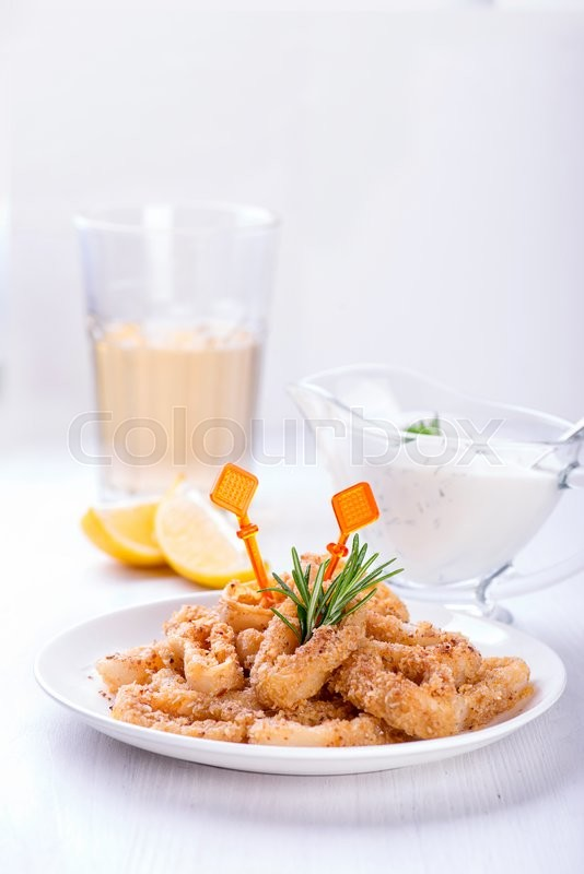 Stock image of 'Fried squid rings with lemon, rosemary and spices'