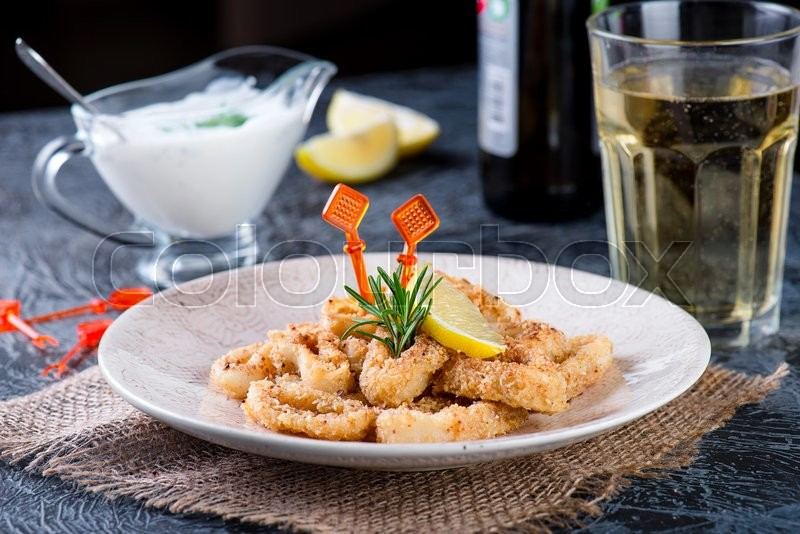 Stock image of 'fried squid rings with lemon, greek yogurt and beer'