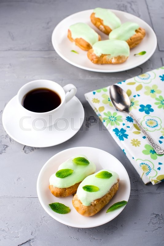 Stock image of 'Cup of coffee and cream dessert eclairs with fresh mint leaves'