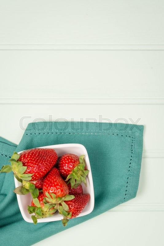 Stock image of 'Appetizing strawberry in the bowl on a wooden background.'