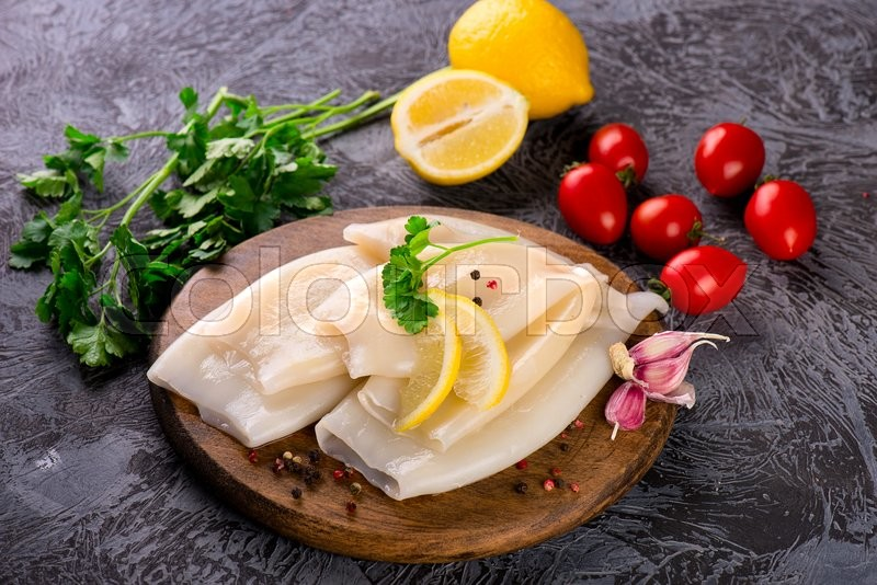 Stock image of 'Preparation of raw squid and ingredients on the wooden board'