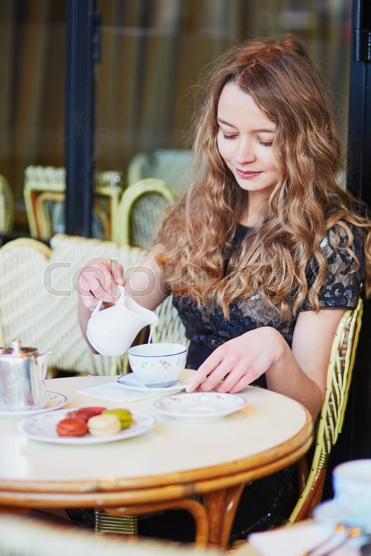 Stock image of 'Beautiful Parisian woman in cafe, drinking coffee and eating macaroons, traditional French dessert'