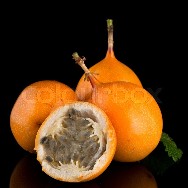 Stock image of 'Passion fruit maracuja granadilla on black background.'
